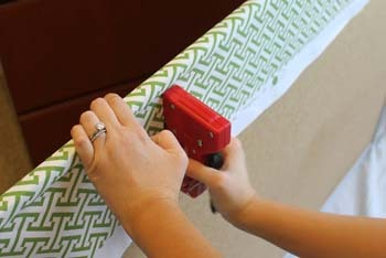 Use a staple gun to secure the fabric at the back of the cork board
