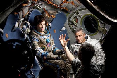 Sandra and George listening to Director Cuaron on set