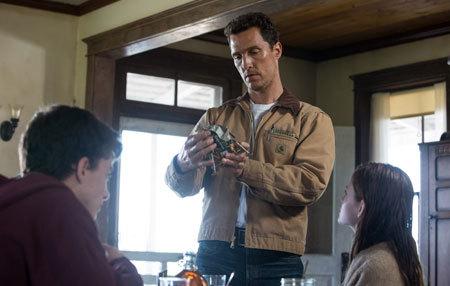 Cooper (Matthew McConaughey) looks at a landing module model