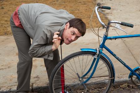 Lloyd (Jim Carrey) tries to pump up a bike tire