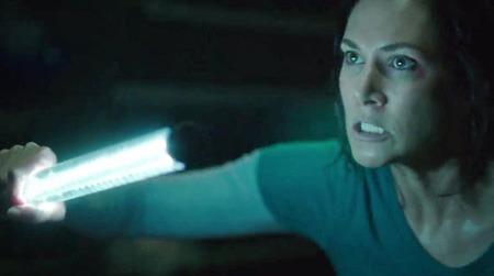 Dr. Walker (Kyra) holds a light on a virus victim