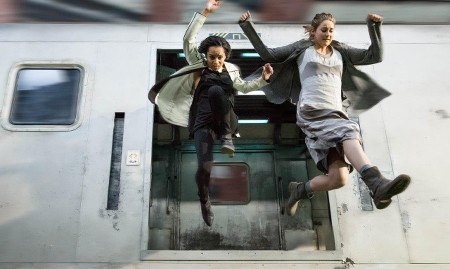Tris and Christina (Zoe Kravitz) jump off a moving train