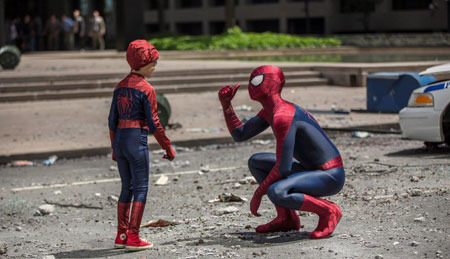 Spider-Man interacts with a kid on the street