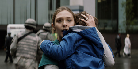 Elle (Elizabeth) protects her son from Godzilla