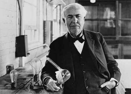 Edison poses with some of his early light bulbs.