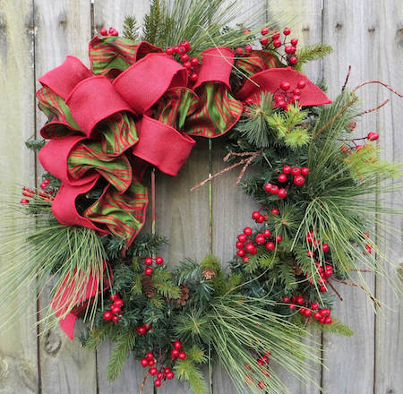 A traditional holiday wreath sometimes includes a bow.