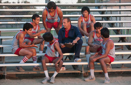 Coach White (Kevin Costner) shares a lighter moment with his running team
