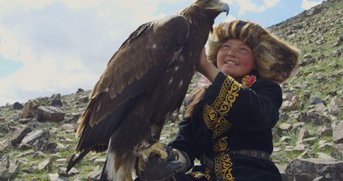 The huntress congratulates her eagle on a great hunt