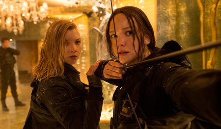 Katniss takes aim while Cressida looks on