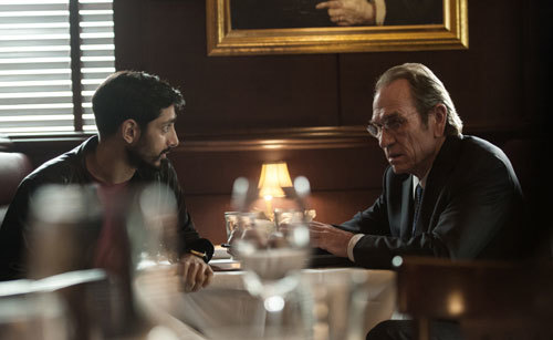 Aaron (Riz Ahmed) meets secretly with Director Dewey