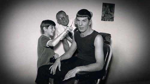 Young Adam helps clip dad's hair