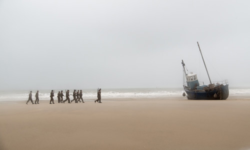 The young soldiers approach the beached boat