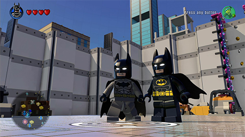 The game's regular Batman standing next to the movie's Batman.