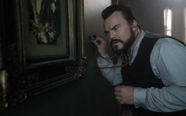 Jack Black as Jonathan listens for the tick in the walls