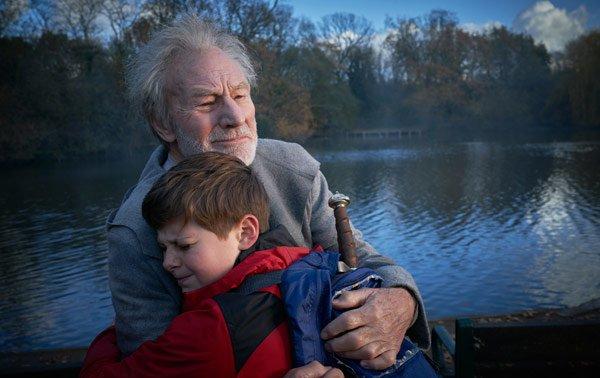 Alex (Louis) is hugged by elderly Merlin