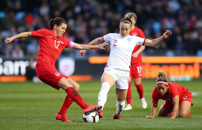 Lucy Bronze of England battles with Christine Sinclair of Canada during the International Friendly