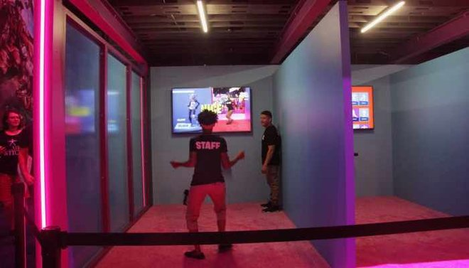 Staff members engage in a Fortnite-themed dance battle during the media hours -- before the display was opened to the public